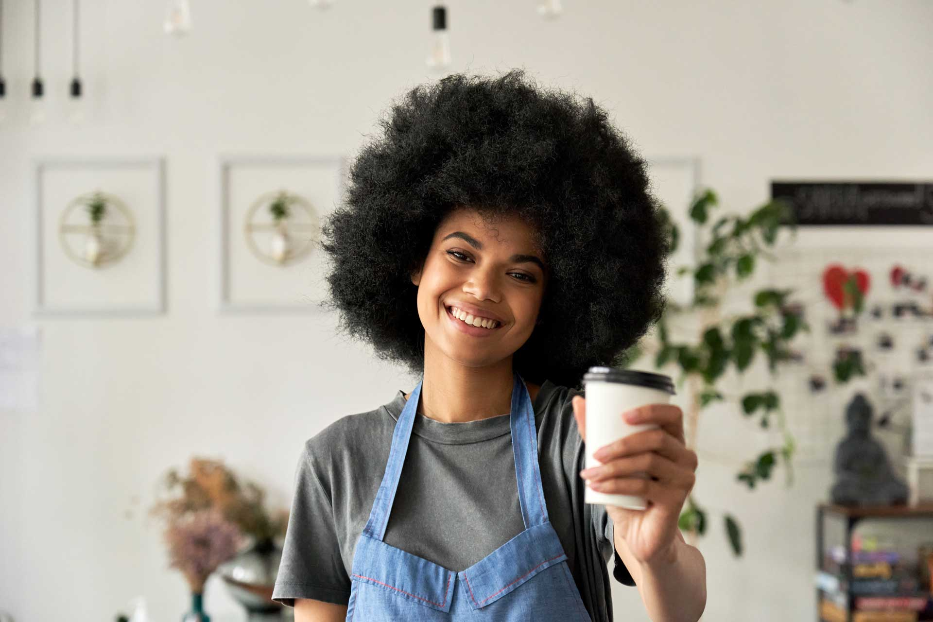 Smiling cafe server with biodegradable coffee cup
